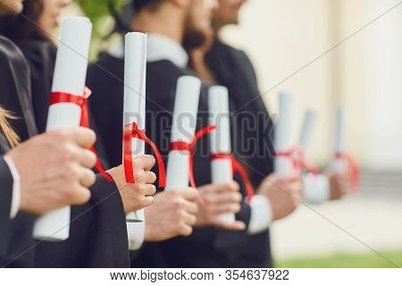 Scrolls Of Diplomas In The Hands Of A Group Of Graduates.