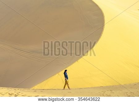 Single Young Asian Girl Walks The Edge Of Sand Dune In Desert At Mingsha Mountain And Crescent Moon