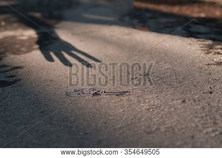 Shadow In The Form Of Hands Reaches Out To The Key Which Lies On The Asphalt. The Ghost Reaches For