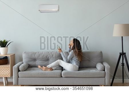 Young Woman Turn On Air Conditioner In Living Room
