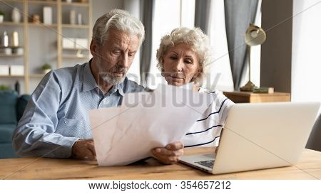 Elderly Husband And Wife Read Documents Pay Bills Online