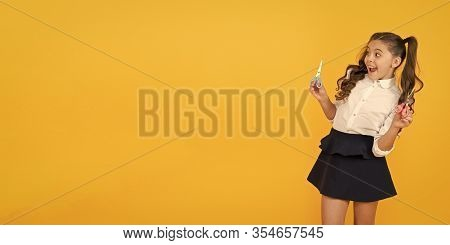 Scissors Developing The Cutting Action. Happy Girl Holding Scissors On Yellow Background. Little Chi