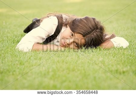 Lovely Relaxed Look. Adorable Girl With School Look Relax On Green Grass. Cute Little Child Have Sch