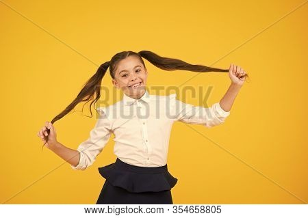 Long And Healthy. Cute Small Schoolgirl Holding Long Hair Ponytails On Yellow Background. Adorable L