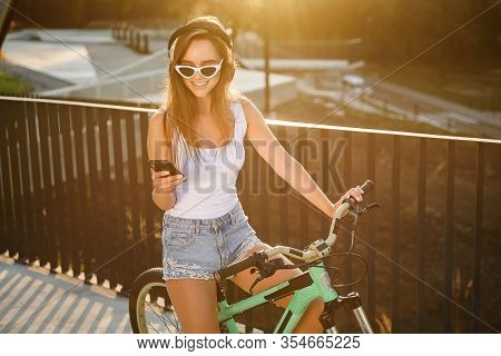 Charming Sexy Girl In Sunglasses And Tempting Clothes Sits On Bicycle And Listens To Music With Earp