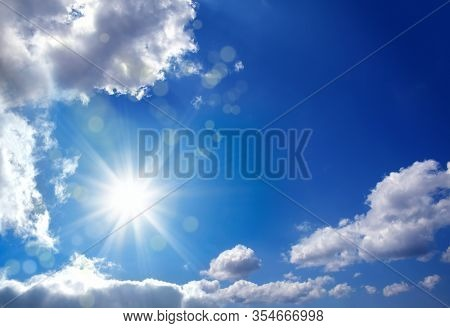 Beautiful shiny blue sky cloudscape image with sun and beam of light