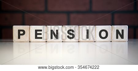Pension Text On Wooden Blocks. Reduction Of Pensions And Payments. Low Pensions Leading To Poverty.