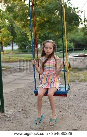 Swing Ride - Swinging Girl. Girl Riding A Swing