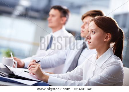 Row of business people attending a seminar and listening closely