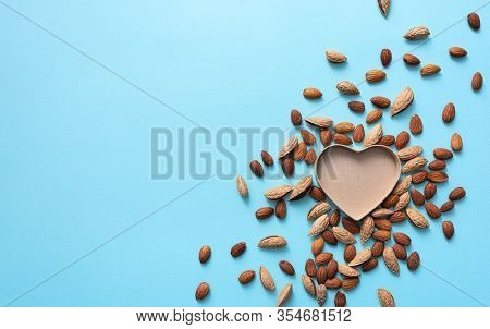 Heart shaped gift box among scattered almond. View from above.