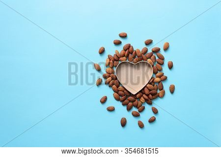 Open and empty heart shaped box with almond around it. Top view background.
