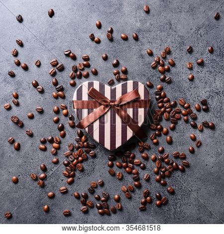 Flat lay of heart shaped gift box on a dark concrete desktop with coffee beans around.