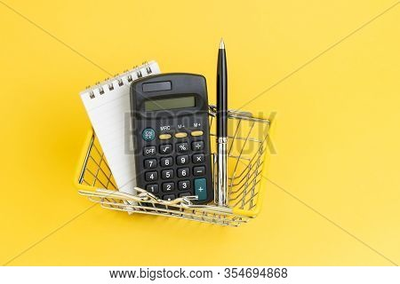 Calculator With Notepad List And Pen In Mini Shopping Basket On Yellow Background, Shopping List, Co