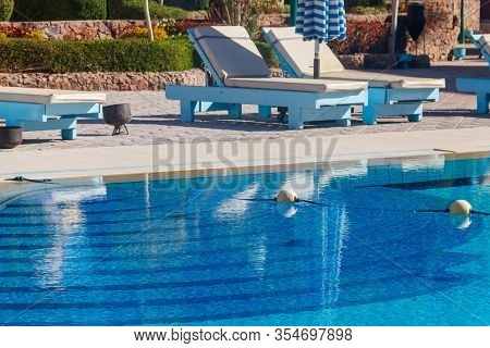 Chaise Longues Near A Swimming Pool. Concept Of Spa, Rest, Relaxation, Holidays, Resort