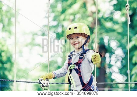 Happy Child Boy Calling While Climbing High Tree And Ropes. Portrait Of A Beautiful Kid On A Rope Pa