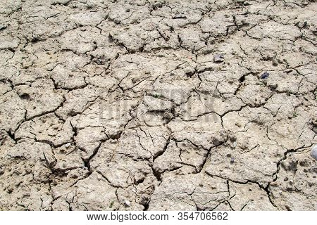 Dried And Cracked Earth Soil From Draught Cracked Terrain Texture In Summer From Climate Change And