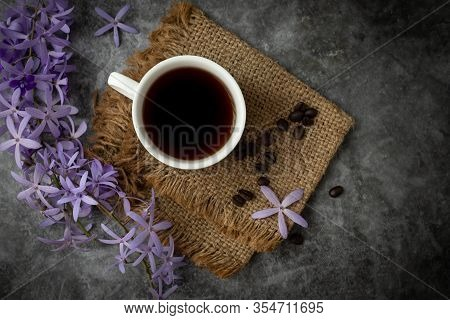 Black Coffee Cup And Flower On Cement Background.