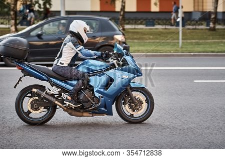 Motorcycle Driver Riding Bike In The City Street. Biker In Helmet Driving Blue Bike. Safety On The R