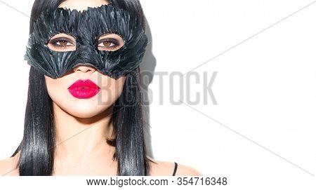 Beauty sexy Glamour brunette Woman portrait. Girl wearing carnival black feather mask. Party. Black hair, red lips, holiday makeup Christmas and New Year celebration, fashion portrait