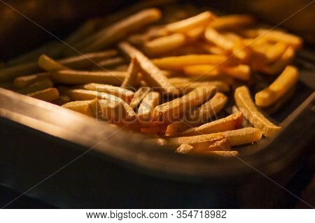 Oven Baked Potato Sticks. French Fries Inside An Oven. Fast Food Potato Skins On A Baking Tray. Seas
