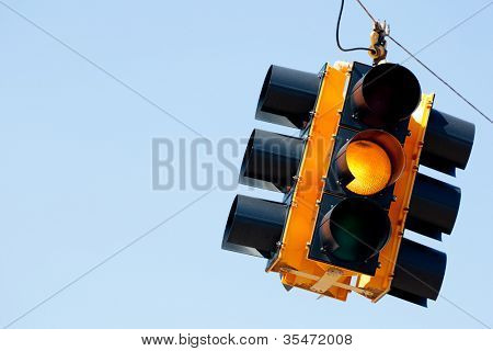 A yellow light traffic signal with blue sky copy space