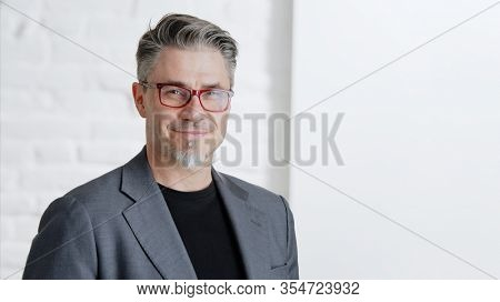 Portrait of happy good looking older businessman in glasses wearing jacket, smiling in front of white background with copy space.  .