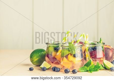 Blueberry And Peach Infused Water, Cocktail, Lemonade Or Tea In Jar With Water Drops. Summer Iced Co