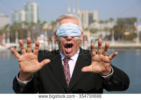 Coronavirus outbreak. COVID-19. A business man is Scared of contracting the Coronavirus as he wears his Paper Face Mask over his eyes instead of his mouth and nose. Coronavirus Hysteria is everywhere