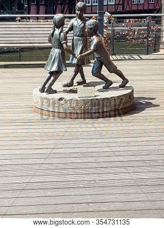LÜneburg, Niedersachsen, Germany - Juli 27, 2018: The Sculpture With The Three Dancing Children In T