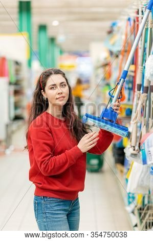 Portrait Of A Young Caucasian Woman Holding A Mop In A Hardware Store. In The Background, The Produc
