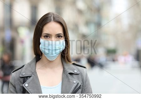 Front View Portrait Of Serious Woman With Protective Mask Avoiding Contagion Looking At Camera On St