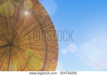 The Sun Shines Through The Umbrella Of Bamboo. Thatch Roof Background, Hay Or Dry Grass Background.