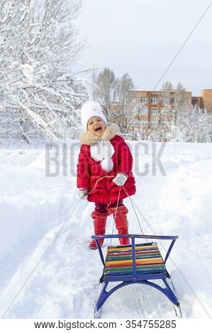 Winter Fun. Beautiful Little Girl In A Red Coat And Mittens Smiles And Holds A Sled On A Rope. Snow