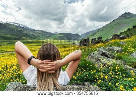 The Girl Lies In A Flowering Field And Looks At The Mountain Landscape