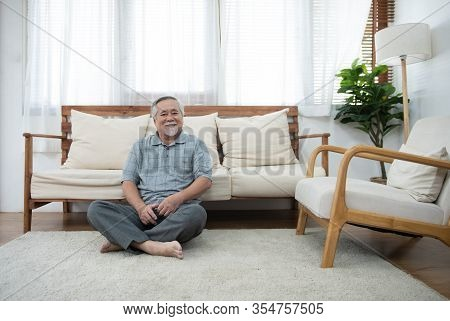 Happy Elder Senior Man In Casual Sit On Carpet Lean On Sofa Look At Camera In Living Room At Home.