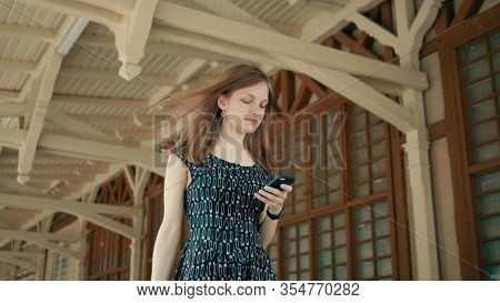 Nice Girl Is Walking On Cinematic Station With Mobile Phone Using App