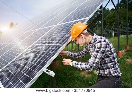 Engineer Connecting Solar Panels On A Green Plantation. Home Construction. Solar Station Development