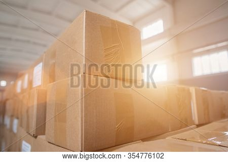 Parcels And Parcels In Cardboard Boxes At The Customs Control Warehouse. The Concept Of Excess Price