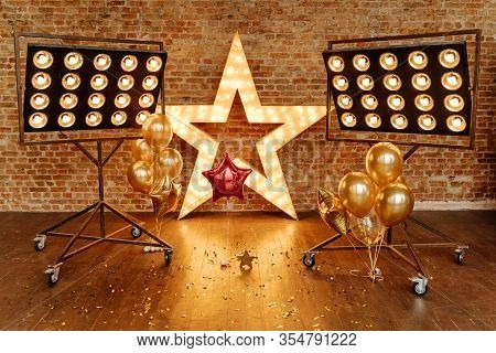 Star Frame With Lamps Decoration And Air Balloons. Scattered Confetti And Professional Illumination