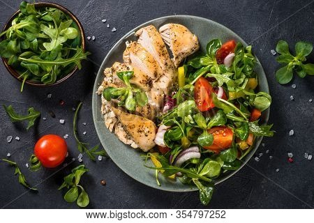Baked Chicken Breast With Green Salad On Black Background. Healthy Food, Keto Diet, Paleo Diet. Top