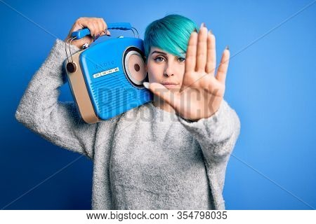 Young woman with blue fashion hair listening to music holding vintage portable radio with open hand doing stop sign with serious and confident expression, defense gesture