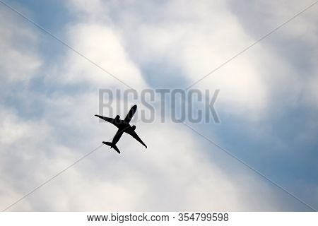 Airplane Flying In The Blue Sky On Background Of White Clouds. Silhouette Of A Commercial Plane Duri