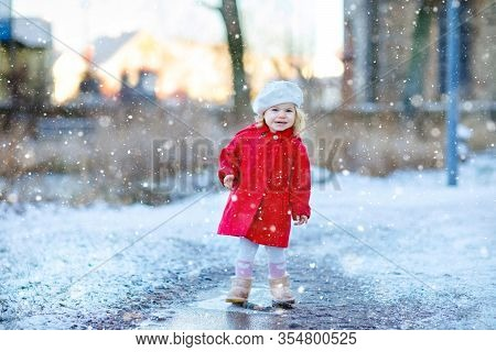 Outdoor Winter Portrait Of Little Cute Toddler Girl In Red Coat And White Fashion Hat Barret. Health