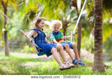 Kids On Swing. Playground In Tropical Resort.