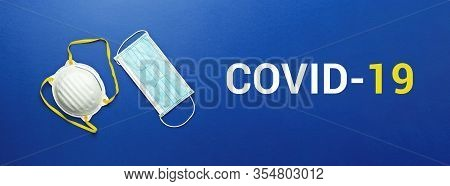 Two Types Of Protective Face Masks On Blue Background With Inscription Covid-19. Protective Masks As