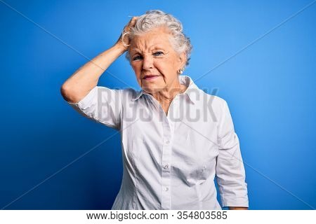 Senior beautiful woman wearing elegant shirt standing over isolated blue background confuse and wonder about question. Uncertain with doubt, thinking with hand on head. Pensive concept.