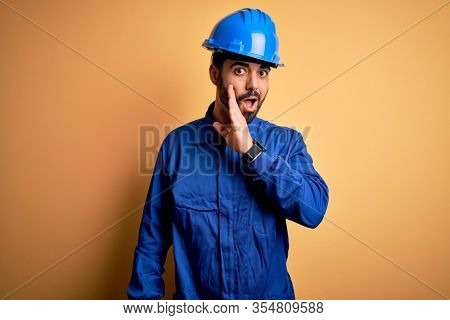 Mechanic man with beard wearing blue uniform and safety helmet over yellow background hand on mouth telling secret rumor, whispering malicious talk conversation