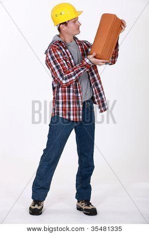 Mason carrying a cinderblock