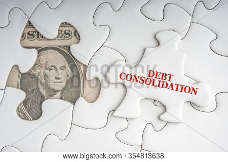 Debt Consolidation Text With Dollar Banknotes On White Jigsaw Puzzle. Business And Copy Space Concep