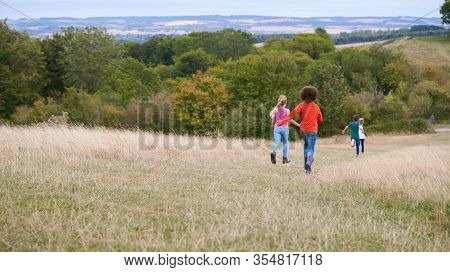 Rear View Of Group Of Children On Outdoor Activity Camping Trip Running Down Hill
